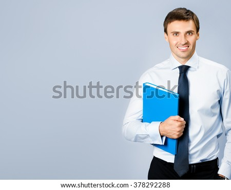 Portrait of happy smiling young business man with blue folder, with copyspace, over grey background - stock photo