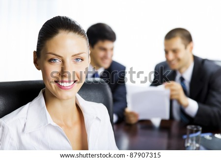 Portrait of happy smiling young business woman and colleagues on background, at office