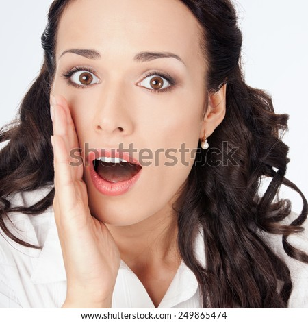 Portrait of happy smiling young business woman covering with hand her mouth, against grey background - stock photo