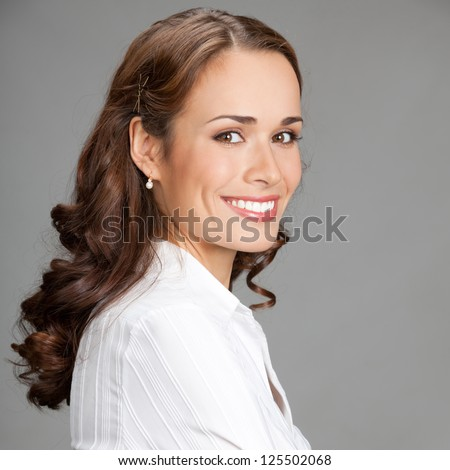 Portrait of happy smiling young business woman, over gray background