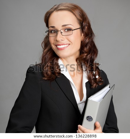 Portrait of happy smiling young business woman with gray folder, over gray background