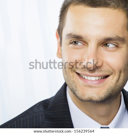 Portrait of happy smiling young businessman at office