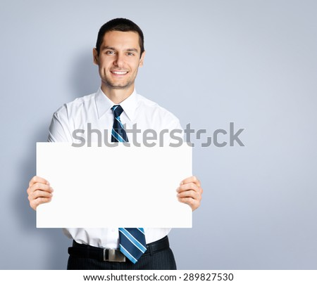 Portrait of happy smiling young businessman showing signboard, against grey background. Copyspace blank area for slogan or text. Business and success concept. - stock photo
