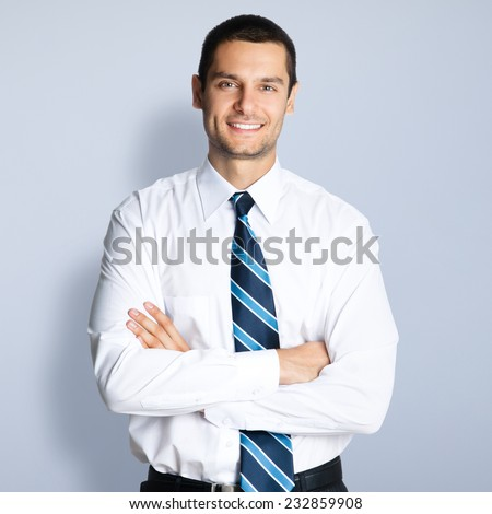 Portrait of happy smiling young businessman with crossed arms pose, against grey background - stock photo