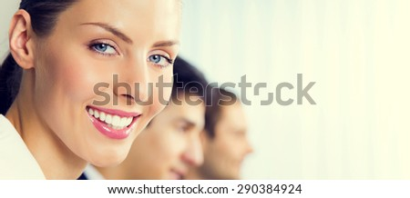 Portrait of happy smiling young businesswoman and colleagues at office, with blank copyspace area for slogan or text - stock photo