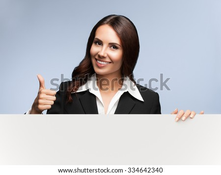 Portrait of happy smiling young businesswoman in black suit, showing blank signboard with blank copyspace area for slogan or text, over grey background, showing thumb up gesture - stock photo