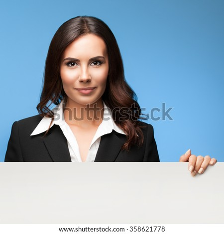 Portrait of happy smiling young businesswoman in black suit, showing blank signboard with blank copyspace area for slogan or text, over blue background - stock photo