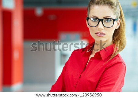 Portrait of happy smiling young businesswoman in office - stock photo