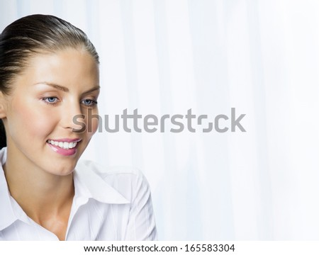 Portrait of happy smiling young cheerful business woman at office, with copyspace
