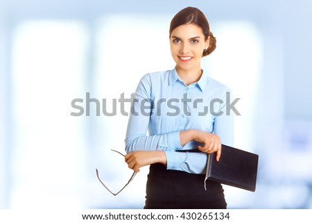 Portrait of happy smiling young cheerful businesswoman in blue shirt and glasses in crossed arms - stock photo