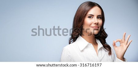 Portrait of happy smiling young cheerful businesswoman, showing okay hand sign gesture, with blank copyspace area for slogan or text message, over grey background