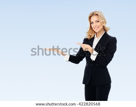 Portrait of happy smiling young cheerful businesswoman, showing something or blank copyspace area for slogan or text message, on blue background