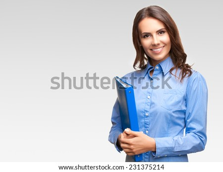 Portrait of happy smiling young cheerful businesswoman with blue folder, against grey background, with copyspace  - stock photo