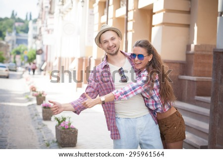 Portrait of happy smiling young couple. Man and woman in fashionable clothes hailing a taxi in the city centre.
