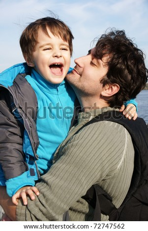 Portrait of happy smiling young father with his little joyful son, outdoor shot - stock photo