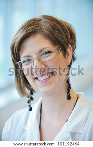 Portrait of happy smiling young female doctor - stock photo