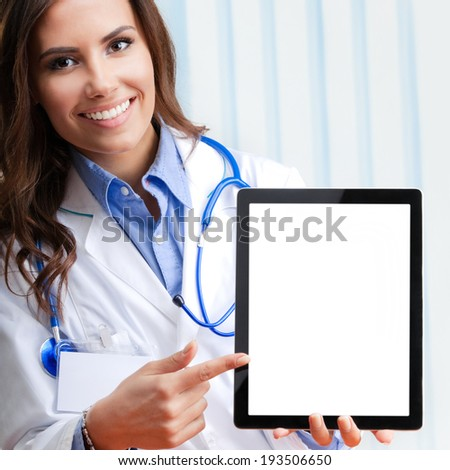 Portrait of happy smiling young female doctor showing blank tablet pc for copyspace, at office - stock photo
