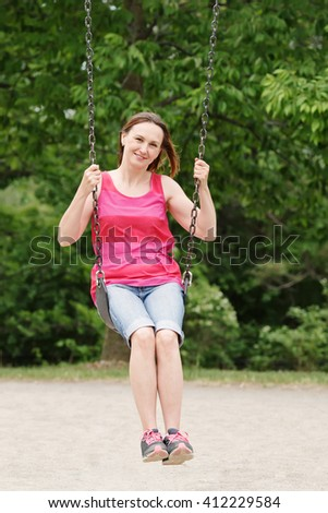 Portrait of happy smiling young middle age woman girl in red tshirt and jeans shorts on swing on backyard playground outside on summer day, lifestyle - stock photo