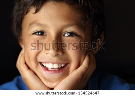 Portrait of happy smiling young school boy with face resting in hands with chiaroscuro lighting - shallow depth of field