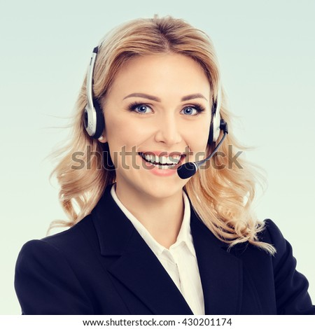 Portrait of happy smiling young support phone operator or businesswomen in headset - stock photo
