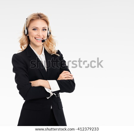 Portrait of happy smiling young support phone operator or businesswomen in headset, on grey background, with blank copyspace area for text or slogan