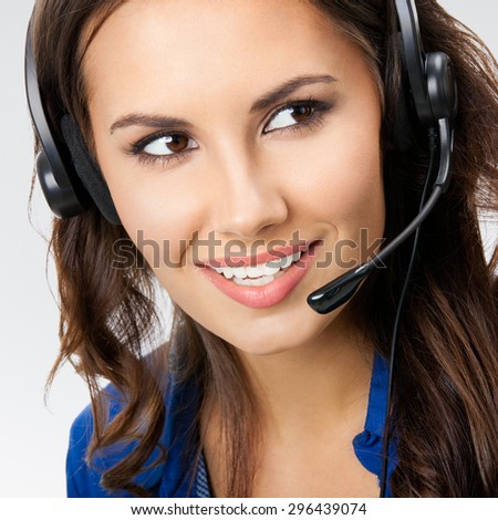 Portrait of happy smiling young support phone operator or businesswomen in headset, posing at studio against grey background - stock photo