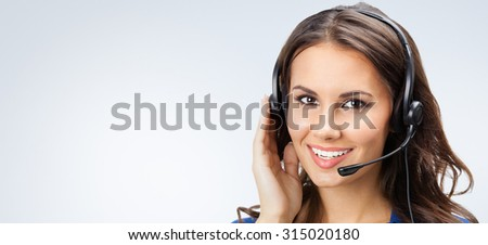 Portrait of happy smiling young support phone operator or businesswomen in headset, with blank copyspace area for slogan or text, posing at studio - stock photo