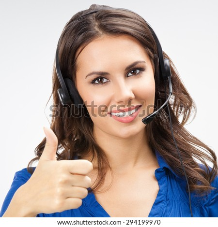 Portrait of happy smiling young support phone operator, showing thumbs up gesture - stock photo