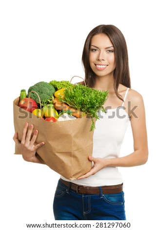 Portrait of happy smiling young woman holding grocery shopping bag with vegetarian raw food, in tank top casual clothing, isolated on white background. Healthy eating and dieting concept.