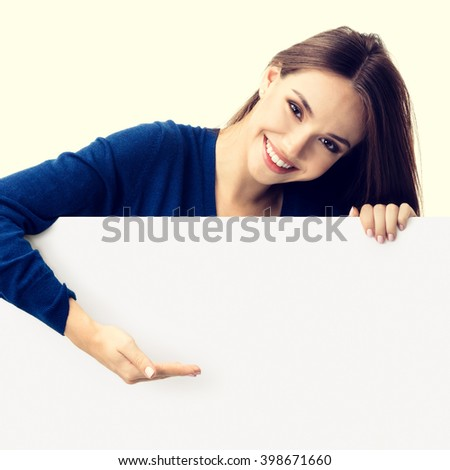 Portrait of happy smiling young woman in blue casual smart clothing, showing empty blank signboard with copyspace area for text or slogan - stock photo