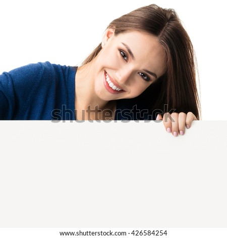Portrait of happy smiling young woman in blue casual smart clothing, showing empty blank signboard with copyspace area for text or slogan, isolated against white background - stock photo