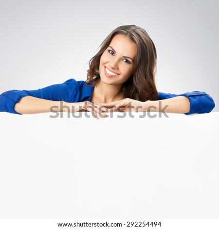 Portrait of happy smiling young woman in blue clothing, showing blank signboard with blank copyspace area for slogan or text, posing at studio against grey background - stock photo
