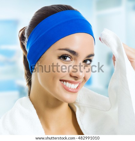 Portrait of happy smiling young woman in fitness wear with towel, at gym