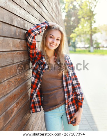 Portrait of happy smiling young woman wearing a casual clothes having fun outdoors in sunny day - stock photo