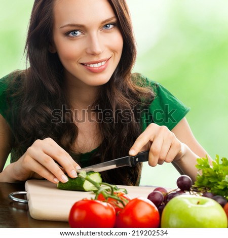 Portrait of happy smiling young woman with vegetarian food, outdoor - stock photo