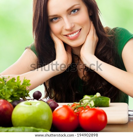 Portrait of happy smiling young woman with vegetarian food, outdoors - stock photo