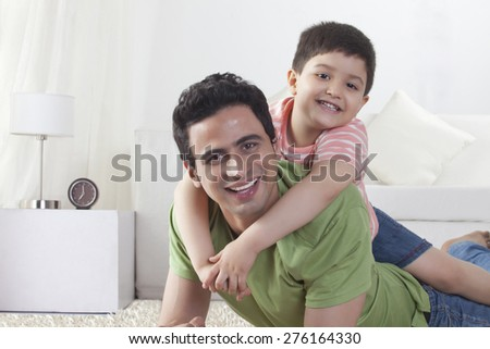 Portrait of happy son sitting on father at home - stock photo