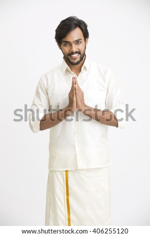 Portrait of happy south Indian man greeting on white background.