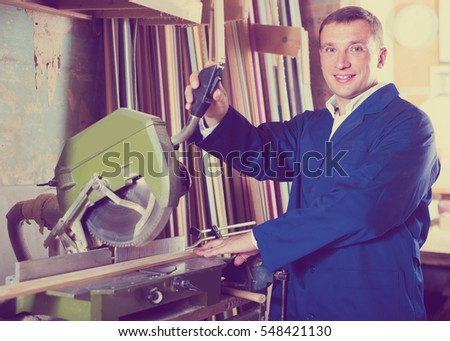 portrait of happy spanish  man in uniform working on electrical rotary saw indoors