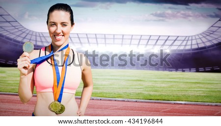 Portrait of happy sportswoman showing her medals against race track