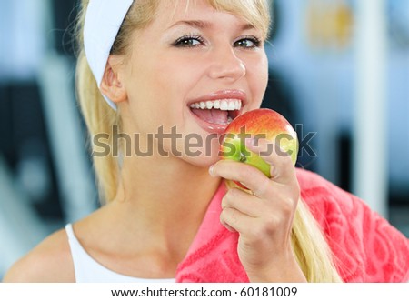 portrait of happy sporty blonde girl eating apple in gym