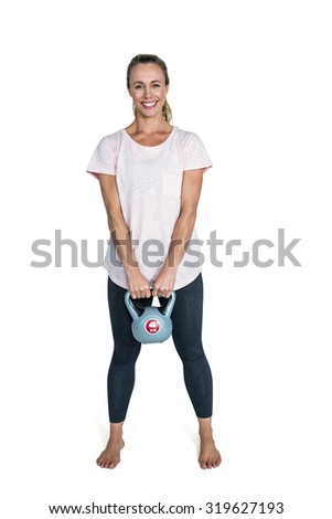 Portrait of happy sporty woman exercising with kettlebell against white background