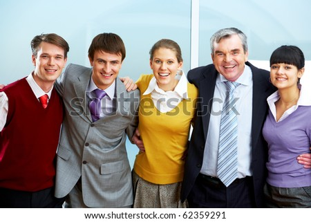 Portrait of happy staff embracing each other - stock photo