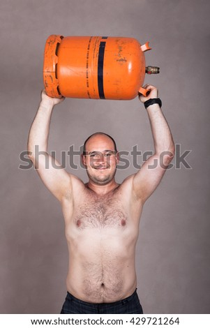 Portrait of happy strong shirtless worker man lifting heavy gas bottle. - stock photo