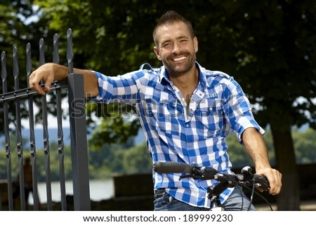 Portrait of happy, stubbly, caucasian, casual man on bicycle outdoor, leaning against fence. Smiling, looking at camera. - stock photo
