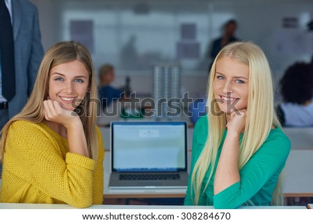 portrait of happy student girls together in classroom, laptop computer in background
