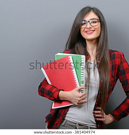 Portrait of happy student woman holding books against gray background - stock photo