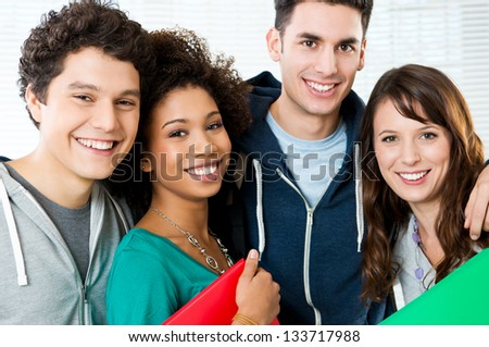Portrait of happy students together at college - stock photo