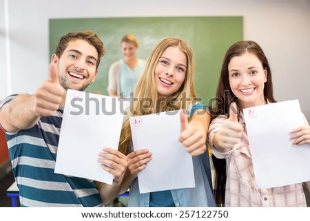 Portrait of happy students with papers gesturing thumbs up in the class - stock photo