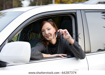 Portrait of happy successful woman with keys from the new car - outdoors